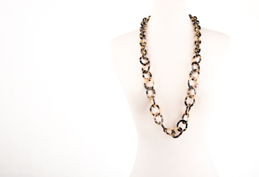 Dark tortoise necklace on white mannequin.